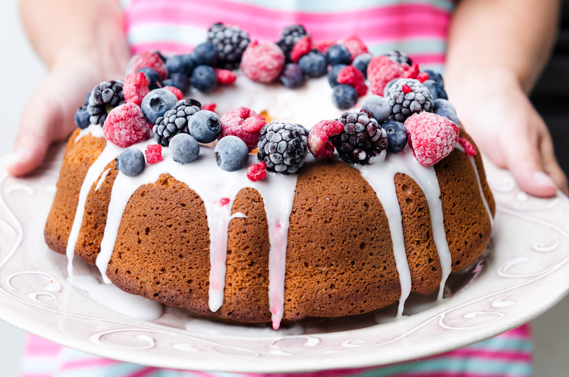 Delicious mixed berry vanilla bundt cake with female hands