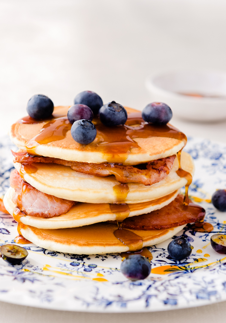 Stack of pancakes layered with bacon, blueberries and maple syru