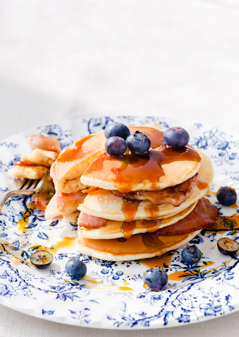 Delicious pancakes stacked with bacon and blueberries
